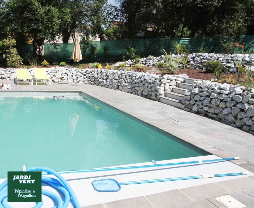 Construction d'une piscine sur terrain en pente, création de terrasses avec murets en pierre sèche, pose d'une terrasse en dallage à Tournefeuille